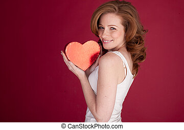 Red Heart For Valentines Day - Smiling woman holding a red...