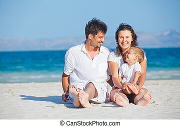 Family sitting on tropical beach