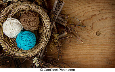 Balls of yarn in a nest easter decoration, on a wooden...