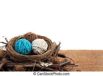 Balls of yarn in a nest, white background - Balls of yarn in...