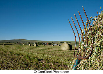 a pitchfork stuck in a bale of hay with a farm landscape in...