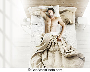 Man in bed from above - Portrait of fit male model asleep in...