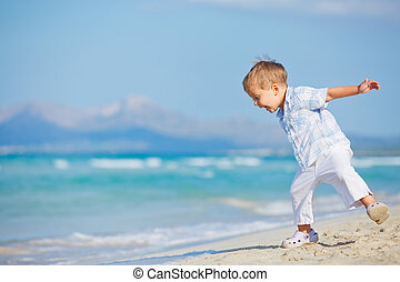 Young cute boy playing happily at pretty beach - Young...