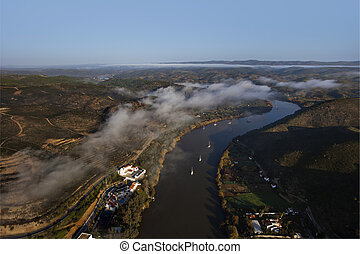 Aerial view over the Guadiana river with clouds