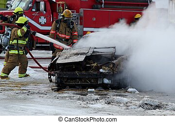 Firefighters putting out a burning car with a hose with...