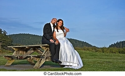 Young Bride and Groom Sitting on Picnic Table