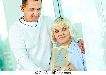 Looking at picture - Portrait of mature man and his wife...