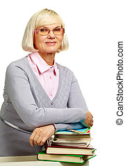 Midage librarian - Pretty elderly lady leaning over a pile...