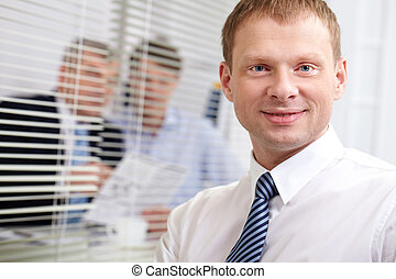 Handsome businessman - Businessman looking at camera with a...
