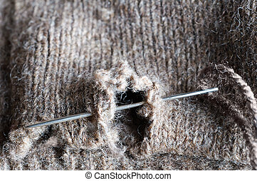 Mending a Hole in Clothing - Close up macro of a threaded...