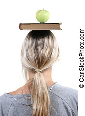 Student with apple and book on the head
