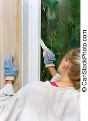 woman restores the window frame color