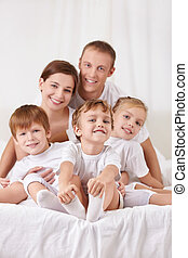Smiling family with children in bed