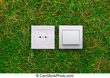 green energy concept: electric outlet and light switch on a...