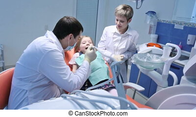 Dental care - Dentist and his assistant treating a little...
