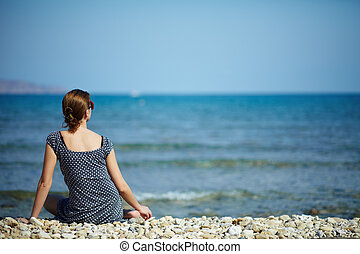 Peaceful moments - Young woman sitting on the beach looking...