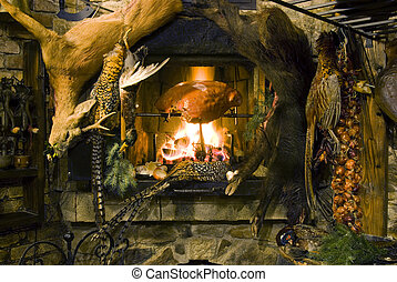 Venison feast - Meat roasting on a fire, venison hanging in...