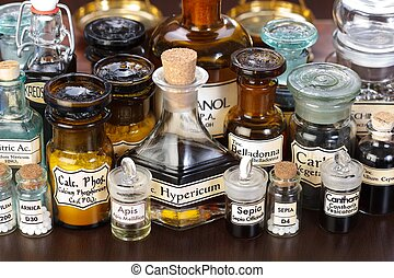Various pharmacy bottles of homeopathic medicine on dark...
