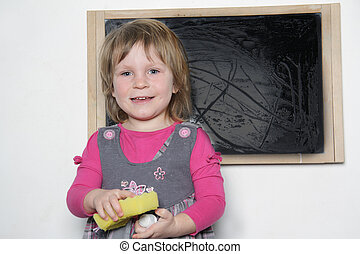young smiling girl near wet school blackboard