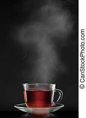cup with hot tea and steam on black