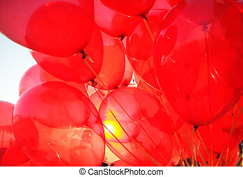 many red balloons flying in the sky