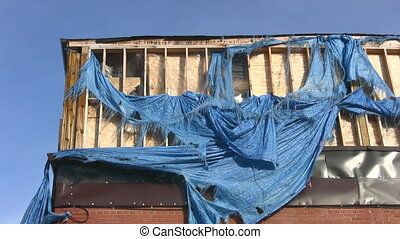 Bad tarp job Two shots - A blue, ripped tarpaulin flaps in...