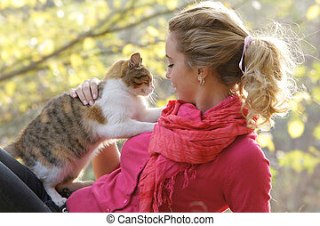 young woman with cat outdoors