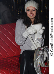 young smiling woman with cup in street cafe at night