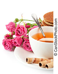 tea in cup with biscuits and bouquet roses - tea in cup with...