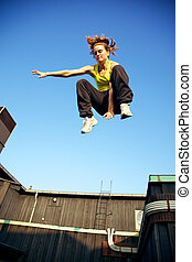 Traceur Demonstrating Parkour - A young traceur in freefall...
