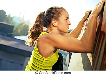 Traceur Doing Parkour - Young woman traceur climbing an...
