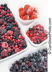 Plastic containers of frozen mixed berries in snow - red...