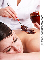 Girl having chocolate body mask . - Young woman having...
