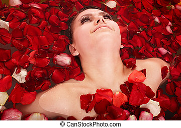 Beautiful girl in jacuzzi with rose petal Body care