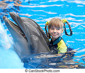 Child and dolphin in blue water - Happy child and dolphin in...