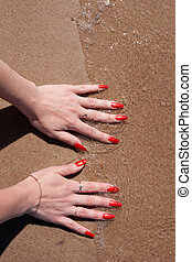 woman hands with red nails in water on the beach