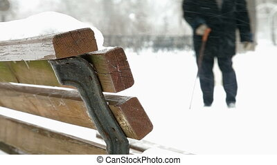 Elderly Woman Walking In Winter Focusing on the Bench DOF
