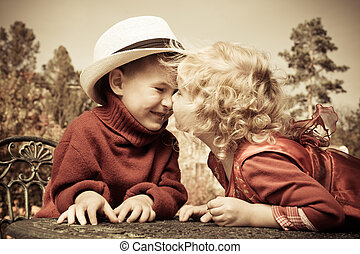kissing children - Romantic children at a park. Retro style.