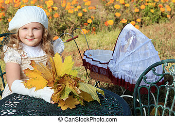leafage - Shot of a cute girl having a rest with baby buggy...