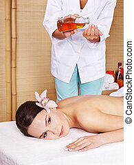 Young woman on massage table in beauty spa.