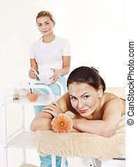 Beautician applying  facial mask by  woman.