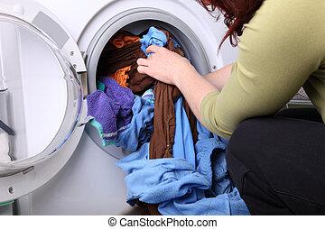woman loading the washing machine in bathroom - woman...