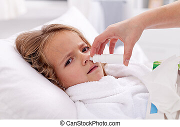 Little girl with bad cold using nasal spray and upset about...