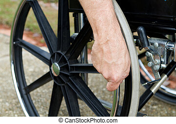 Hand On Wheelchair - Disabled man's hand grips the push rim...