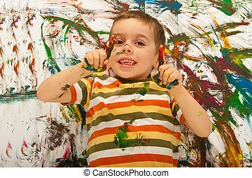 Messy painted boy pointing up and lying down on painted...