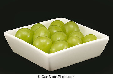twelve grapes of luck in tub, isolated on black