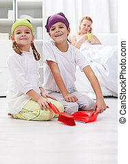 Kids cleaning the room helping their mother