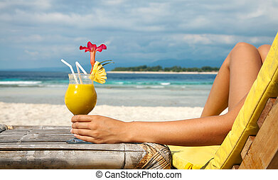 Holding a cocktail on a tropical beach - Woman holding a...