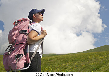 High up in the mountains - A young female tourist hiking...