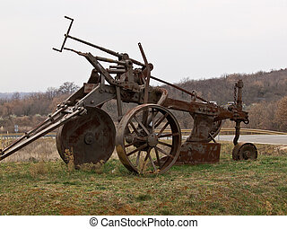old plough - old big rusty plough parked as a monument